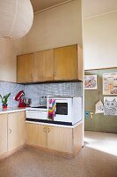 Simple retro kitchen area with electronic appliances on base units and pale wooden wall units
