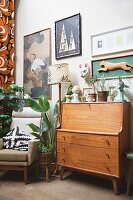 Retro wooden bureau below gallery of pictures and framed carved animal figurine