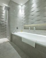 Bathtub in designer bathroom with marble tiles and 3D structured tiles