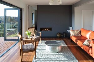 Antique chair and leather sofa around round coffee table on rug in front of fireplace in dark grey partition wall; open folding terrace doors with view of wooded landscape