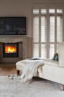 White chaise longue, fire in fireplace and interior shutters on French windows in elegant bedroom