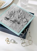 Black and white photo of chains and rings on silver-grey velvet decorating lid of jewellery box