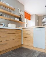 Corner of kitchen counter with solid wooden drawers below glasses on wooden shelves mounted on wall painted pale grey