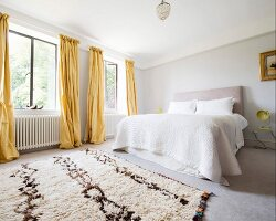 View across rug to double bed and yellow floor-length curtains on windows in simple bedroom