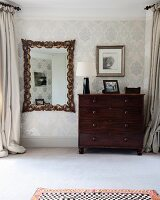 Antique wall mirror with elaborate frame next to dark wooden chest of drawers against ornately patterned wallpaper