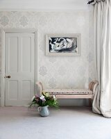 Bouquet in jug on floor next to antique bench against wall covered in ornate wallpaper