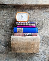 Alarm clock and stacked books on vintage stone bracket on stone wall