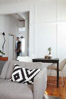 Cushion with graphic pattern on grey sofa in front of small dining table and retro chairs
