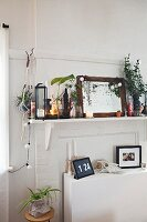 Shelf crammed with ornaments above white sideboard