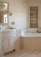 Elegant country-house bathroom with corner bathtub and fitted washstand