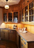 Elegant, rustic, country-house kitchen with glass-fronted wall cabinets, bottles of wine and silver jug