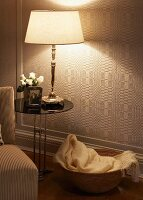 Lit table lamp on side table in front of geometric wallpaper