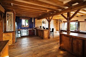 Spacious, country-house kitchen and dining area with wood-beamed ceiling and supporting structure