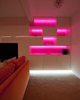 Fitted cabinets with shelf compartments illuminated bright pink behind orange sofa in dark interior