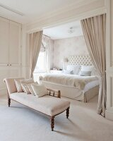 Chaise longue and sleeping alcove screened by curtains in glamorous bedroom