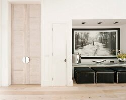 Oriental double doors, picture and pouffes in niche in minimalist foyer