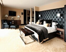 Bed with black upholstered headboard, bench and reading chair in masculine bedroom