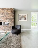 Leather armchair on pale grey flokati rug in front of fireplace in stone chimney breast in modern interior