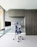 Office chair at L-shaped glass table next to fitted cupboards with grey and brown striped veneer in elegant study