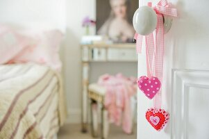 Pink hearts on ribbons hanging from doorknob and view into romantic bedroom