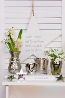 White hyacinths, snowdrops and silver-coloured containers below motto written on star-shaped decoration