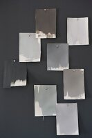 Colour-chart cards in various shades of grey hanging on wall