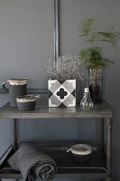 Various ornaments in shades of grey on side table against grey wall