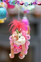 Monkey toy with feminine clothing hanging from string of colour beads as Christmas decoration
