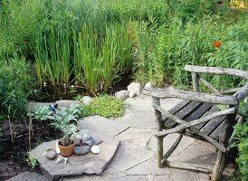 Stone-flagged seating area in garden next to small pond and bog garden