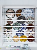 Colourful decorative wall plates in display case