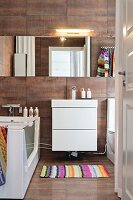 White washstand below mirrored cabinet in modern bathroom with rust-coloured tiles