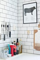 Kitchen utensils on shelf below collection of knives on white subway tiles