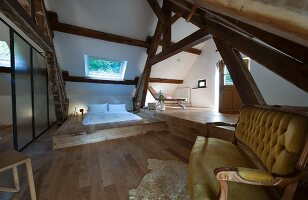 Modern futon on platform, partition, antique sofa and rustic roof beams in renovated attic
