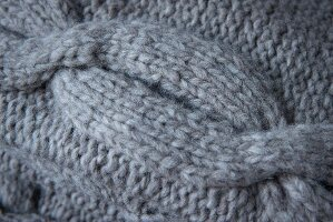 A knitted cable pattern made from grey mixed yarn (close)