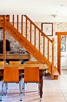Wooden staircase, stone wall and tiled floor in dining area