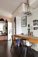 Narrow table made of pale wood and black bar stools below collection of photos on wall