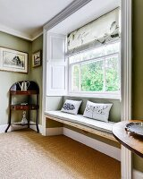 Window seat in large window niche next to antique quarter-round corner table