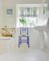 White tiled floor, pedestal sink and wooden chair painted purple below lattice window in rustic bathroom
