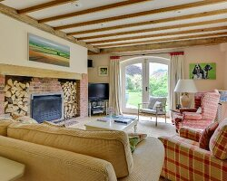 Wood-beamed ceiling above sofa and armchairs around fireplace with firewood store in living room