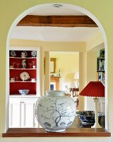 Exquisite vase on sill of arched interior aperture with view of dresser next to open door