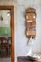 Old cigar boxes mounted on wooden board repurposed as organizer with key rack