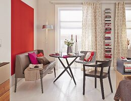 A leather bench and various chairs around a round table against a red painted wall in a one-room apartment