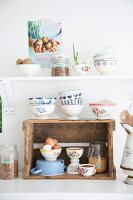 Rustic wine crate used as kitchen shelf and stacked white and blue bowls below white shelf in vintage-style ambiance