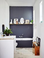 Floating shelf on dark grey wall and masonry washstand in minimalist bathroom
