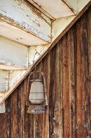 Old glass lantern hanging on nail under staircase against wooden façade