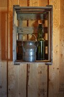 Old milk churn and swing-top bottle decorating fruit crate hung on wall of wooden house