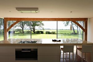 View across free-standing kitchen counter through panoramic window to green landscape