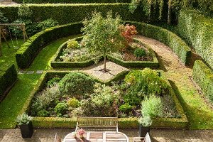 View down onto elegant garden with herbaceous borders surrounded by clipped hedges