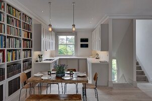 Square, rustic wooden table, vintage chairs and bookcase in front of white fitted kitchen with panelled fronts