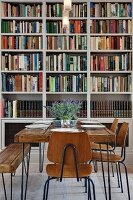 Square rustic wooden table and vintage chairs in front of bookcase